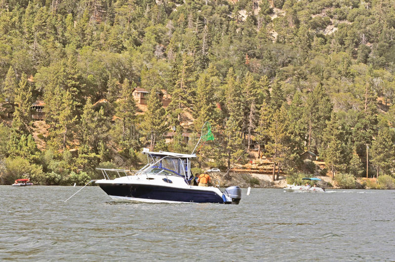 Fishing Lesson. A grandfather has anchored his Robalo at the west end of Big Bear Lake and is teaching his grandson to fish. The net is handy just in case a fish stock photography