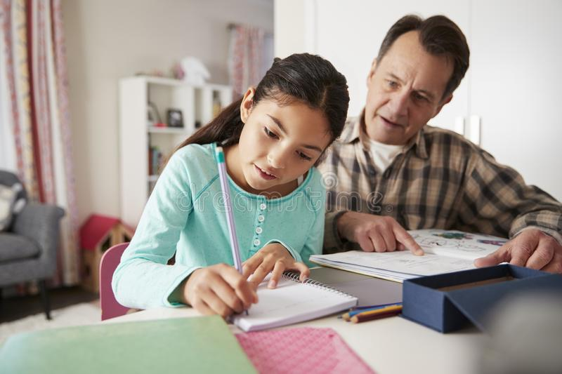 Grandfather Helping Granddaughter With Homework Sitting At Desk In Bedroom royalty free stock photography