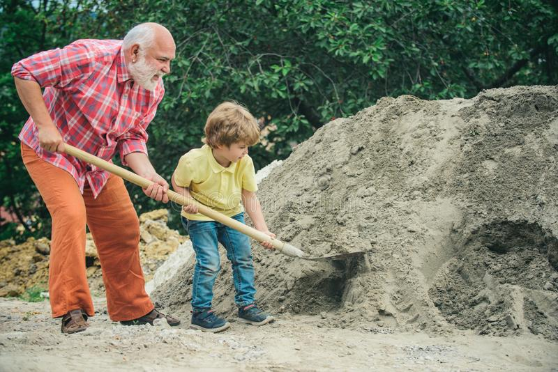 Grandfather with his grandson hard working. Little grandson helping his grandfather with building work. Child and works royalty free stock photo