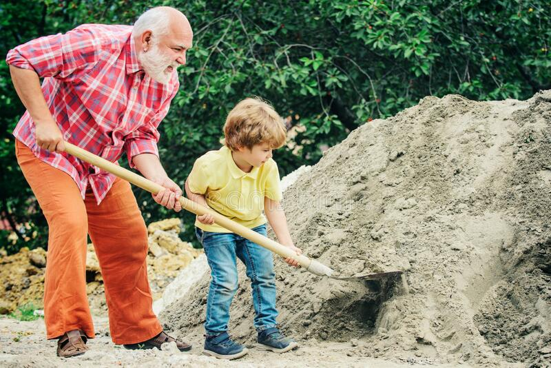 Grandfather with his grandson hard working. Little grandson helping his grandfather with building work. Child and works royalty free stock image