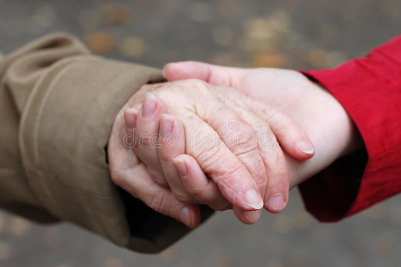 Grandfather holding his grand daughter hand stock photos