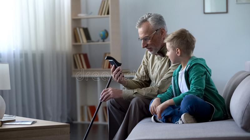 Grandfather holding phone, boy helping him to acquaintance with new technologies royalty free stock photo