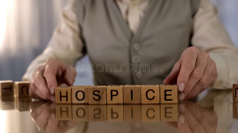 Grandfather making word hospice of wooden cubes on table, elder care, disorder. Stock photo stock photography