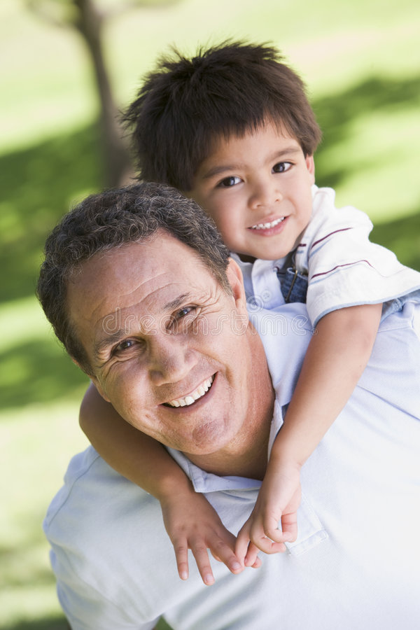 Grandfather piggyback riding grandson stock photo