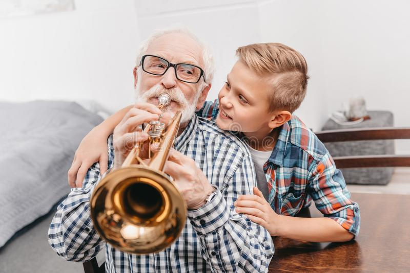 Grandfather playing trumpet while smiling boy royalty free stock image