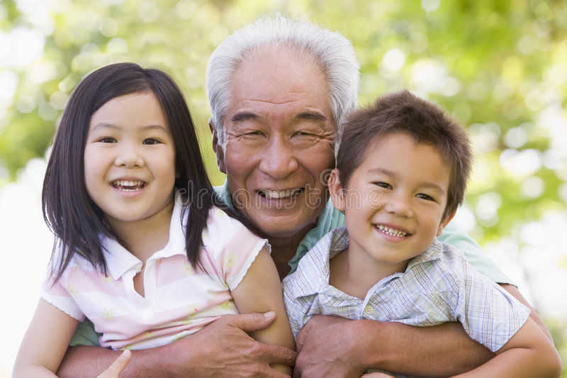 Grandfather posing with grandchildren stock images