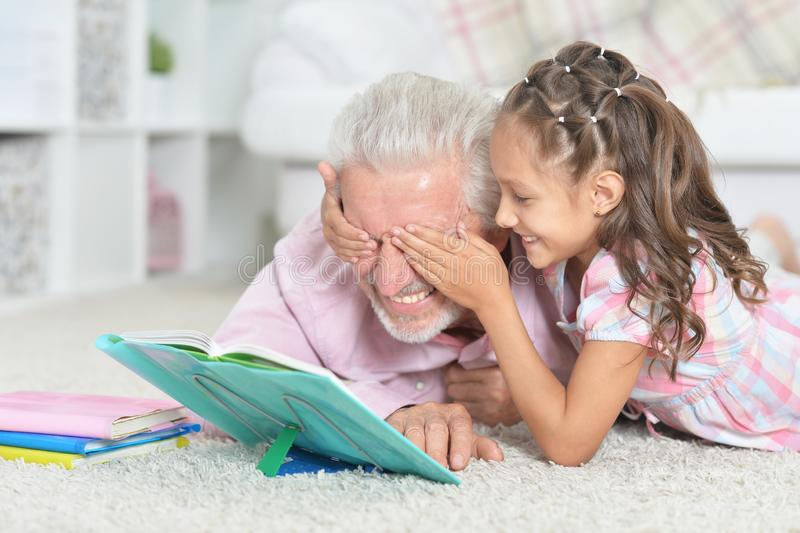 Portrait of grandfather reading book with his little granddaughter. Grandfather reading book with his little granddaughter at home royalty free stock photo