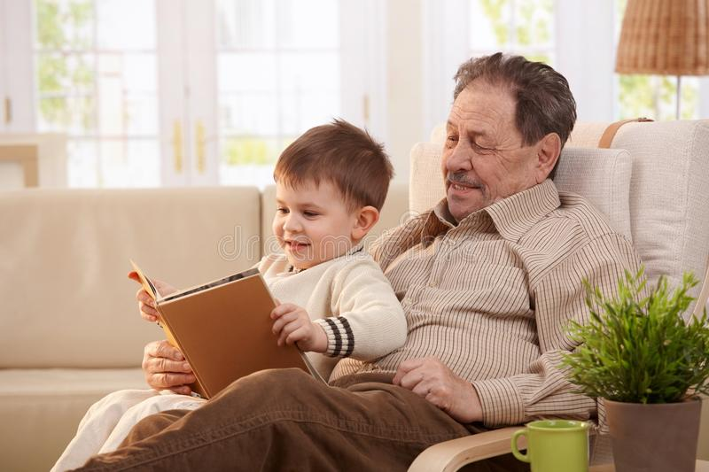 Grandfather reading tales to grandson. Grandfather sitting in armchair and reading tales to grandson stock photo