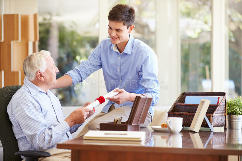 Grandfather Showing Document To Teenage Grandson. Grandfather Showing Precious Document To Teenage Grandson Putting Hand On Shoulder stock photo