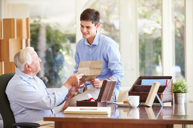 Grandfather Showing Document To Teenage Grandson. Smiling At Each Other royalty free stock image