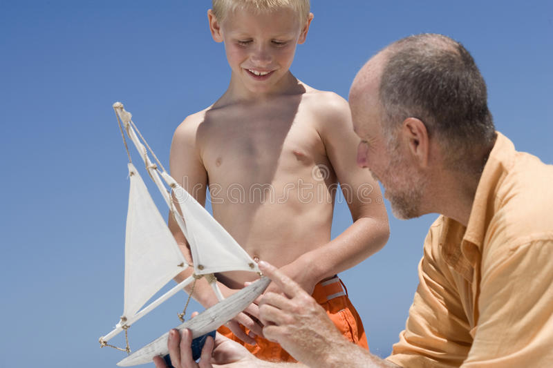 Grandfather showing grandson model sailboat royalty free stock photos