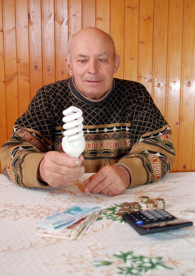 The grandfather sits at a table on which to lie the calculator and money, paper notes and coins. He holds an energy saving lamp in hand. Economy of the budget stock photography
