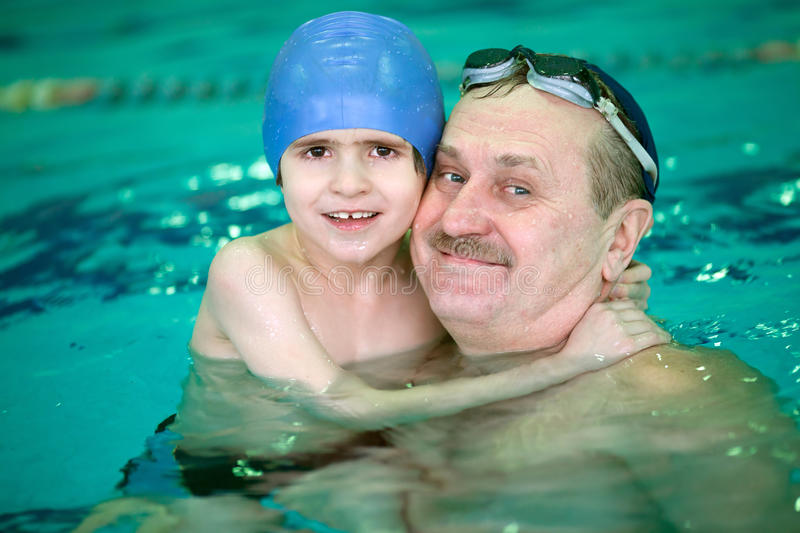Grandfather with small boy in swimming pool royalty free stock photography