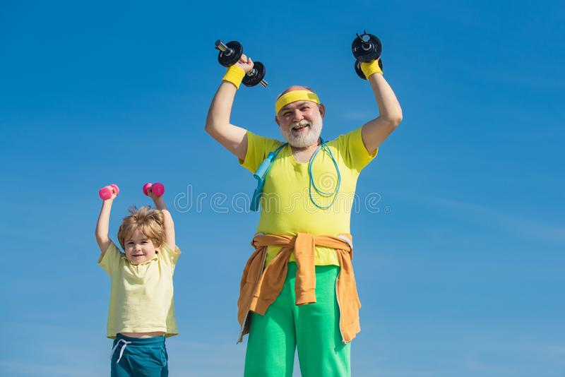 Grandfather and son doing exercises. Father and children having workout. Senior man and child in family health club. Sports for kids royalty free stock image