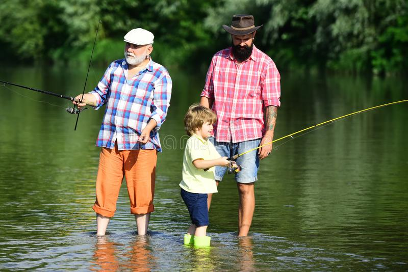 Grandfather with son and grandson having fun in river. Father, son and grandfather on fishing trip. Men hobby. stock photography