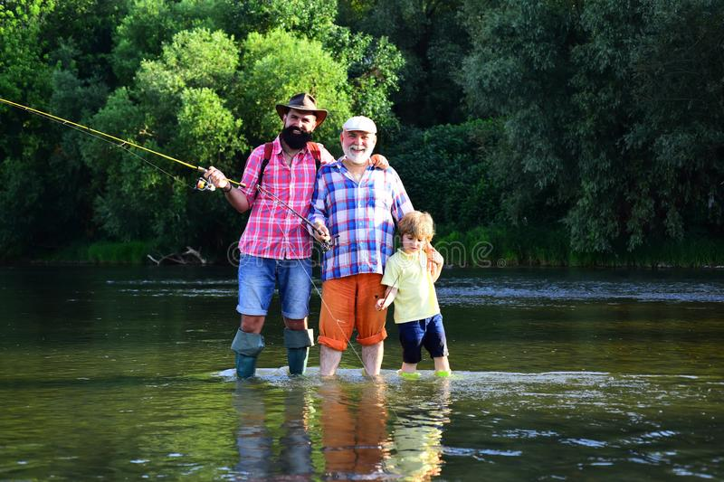 Grandfather with son and grandson having fun in river. Happy fathers day. Grandson with father and grandfather fishing. By lake royalty free stock images