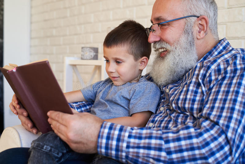 Grandfather supporting his kid to read a book while sitting in a royalty free stock photo