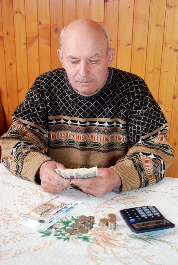 The grandfather in a sweater sits at the dacha at a table and counts money. The elderly man at a table with the calculator considers coins and banknotes stock photography