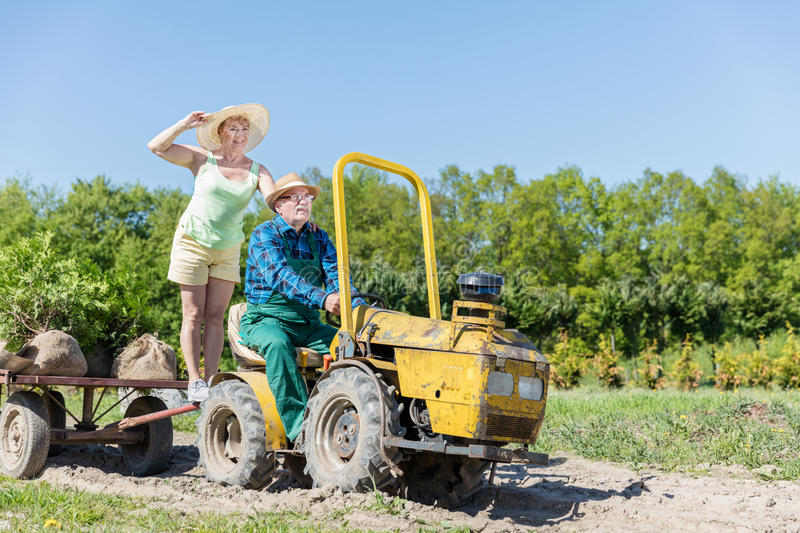 Grandfather taking grandmother for ride on tractor trailer across countryside royalty free stock photo