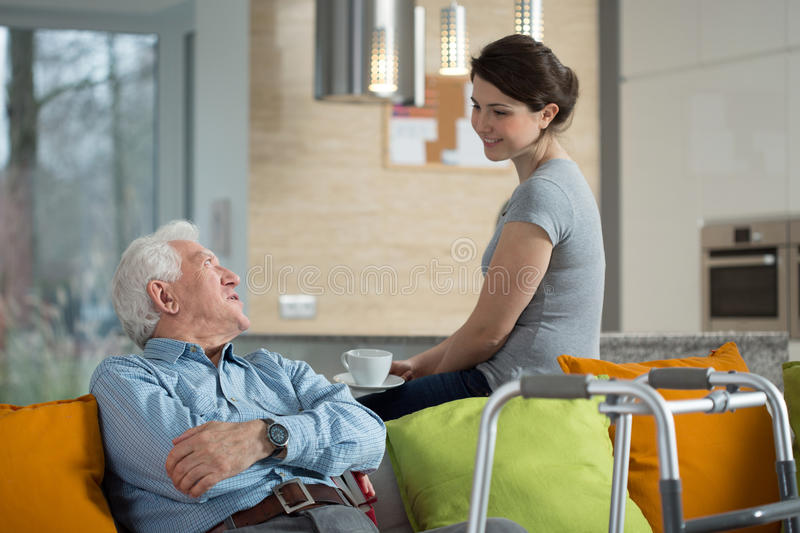 Grandfather talking with loved granddaughter. In his home stock photo