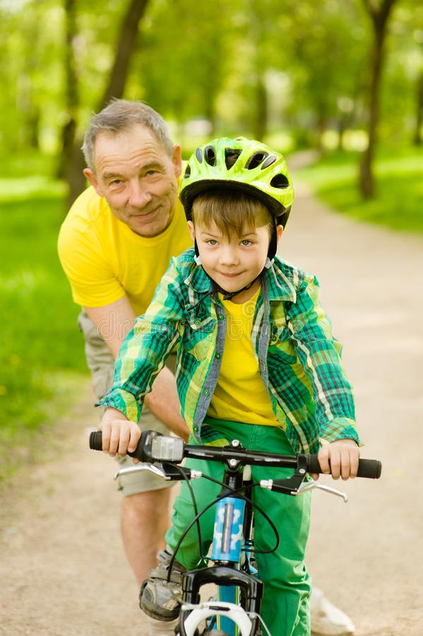 Grandfather teaches his grandson to ride a bike stock image