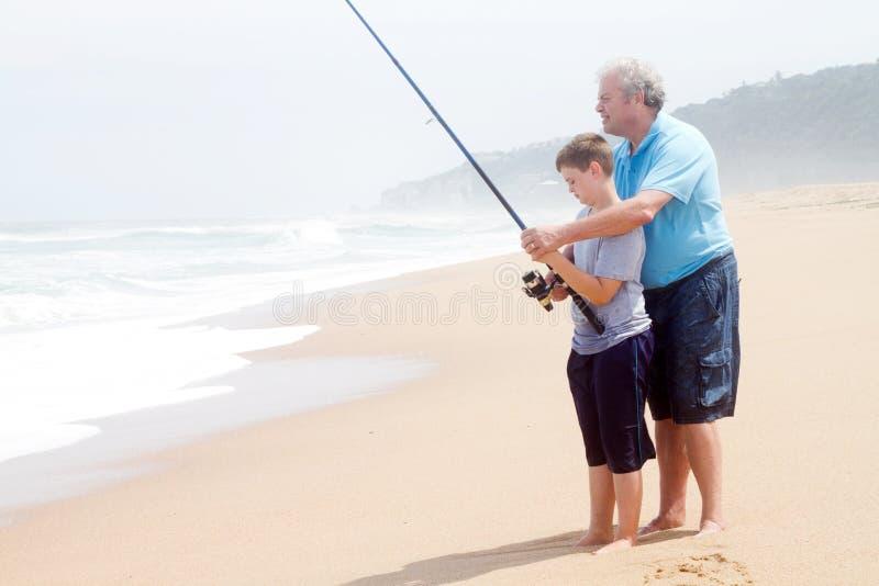 Grandfather teaching grandson fishing. Grandfather teaching teen grandson fishing on beach royalty free stock image
