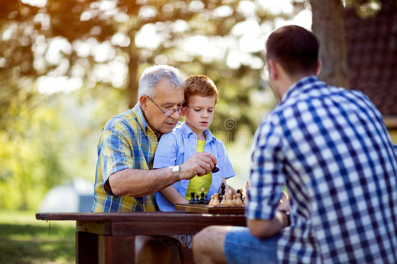 Grandfather teaching his grandson chess royalty free stock images