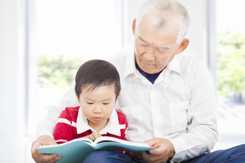 Grandfather telling story to his grandson. At home royalty free stock photos