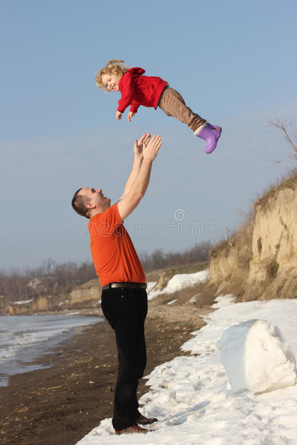Grandfather Throwing His Granddauther In The Air Stock Photo