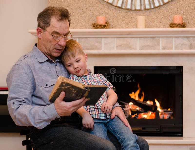 Grandfather to his grandson reading a book by the fireplace.  stock photo