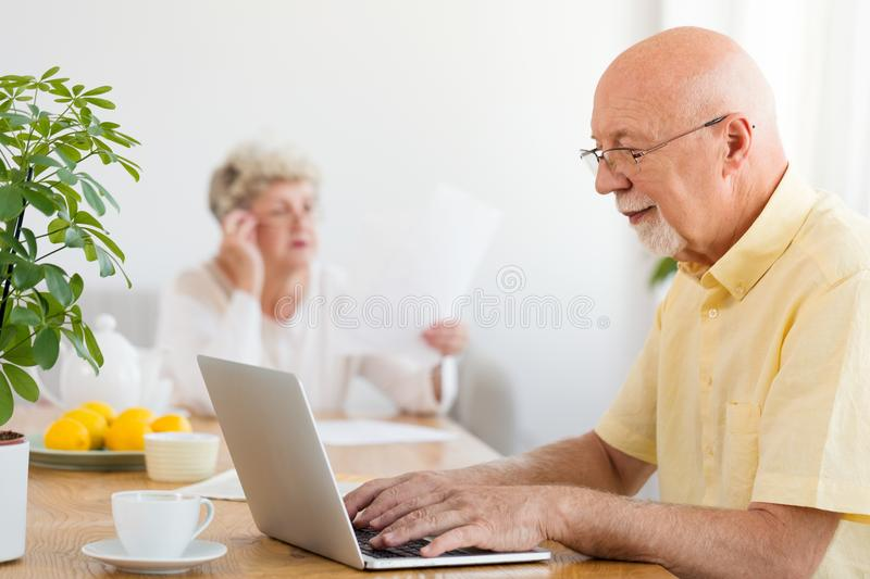 Grandfather using laptop at home. The problem of Internet addict royalty free stock images