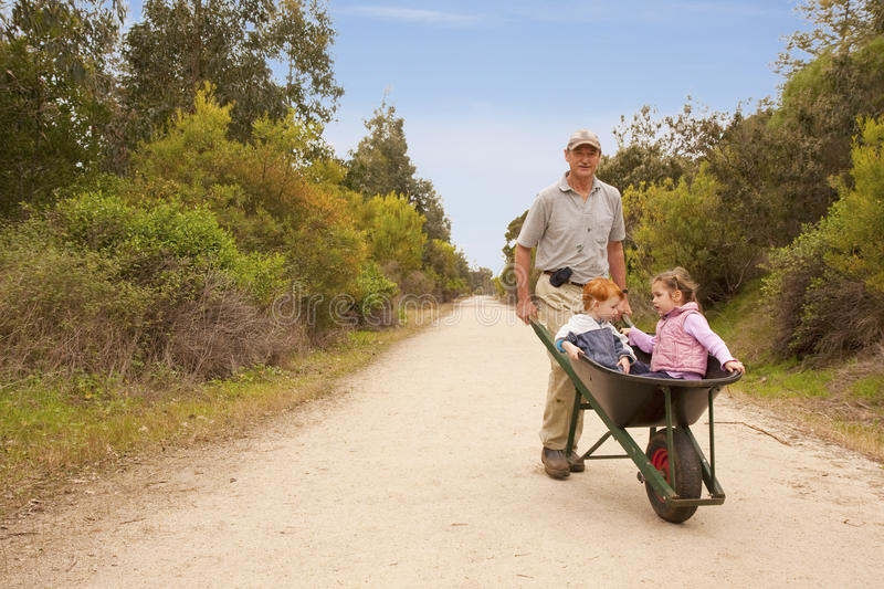 Download Grandfather Walking Grandkids In Wheelbarrow Stock Image - Image: 11239277