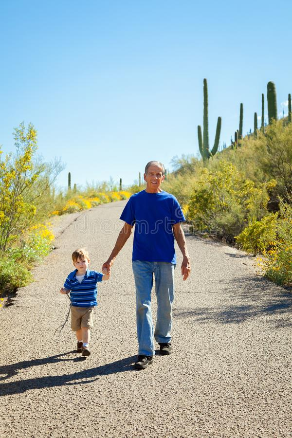 Grandfather and Young Grandson Hike Downhill, Holding Hands on a royalty free stock photo