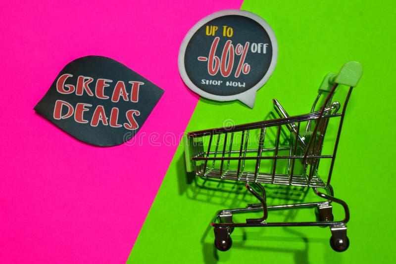 Grandi affari e fino a -60% fuori dal testo e dal carrello del negozio ora fotografie stock libere da diritti