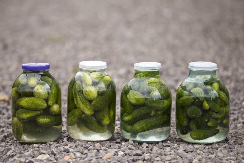 Grandi barattoli di vetro con i cetrioli freschi verdi dei sottaceti salati nel Mari fotografia stock libera da diritti