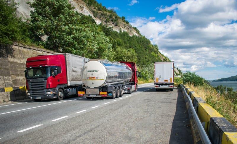 Grandi camion che portano i prodotti differenti, su una bella strada della montagna, un giorno di estate Vicino alla strada è un  fotografia stock libera da diritti