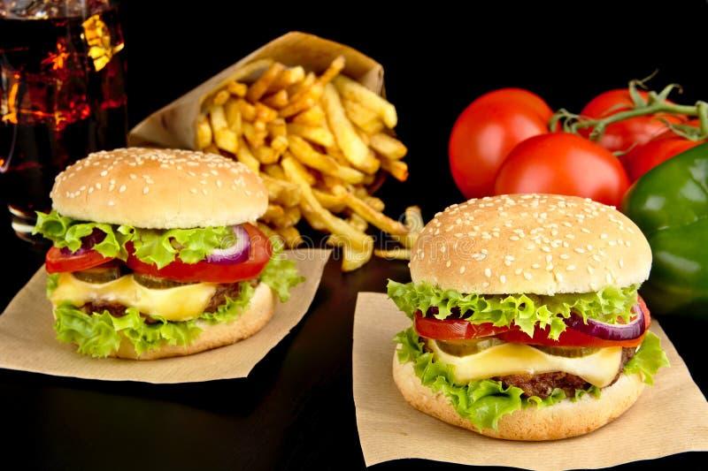 Grandi cheeseburger su carta, sulle patate fritte e sul vetro di cola sul nero immagini stock