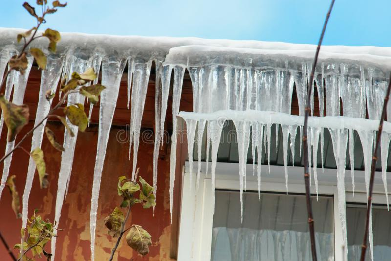 Grandi doppi ghiaccioli che appendono dal tetto e sopra una finestra di plastica contro il cielo blu fotografia stock