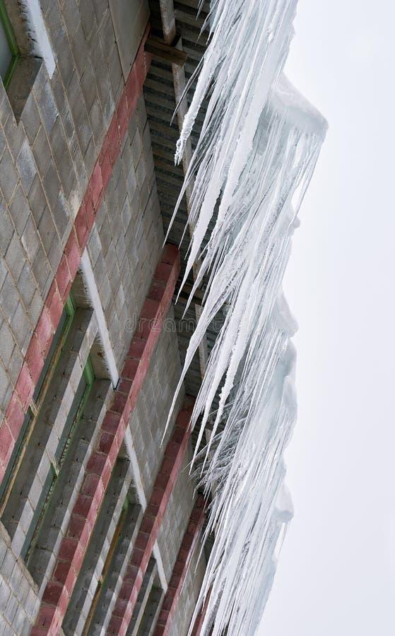 Grandi ghiaccioli che appendono sul tetto fotografie stock