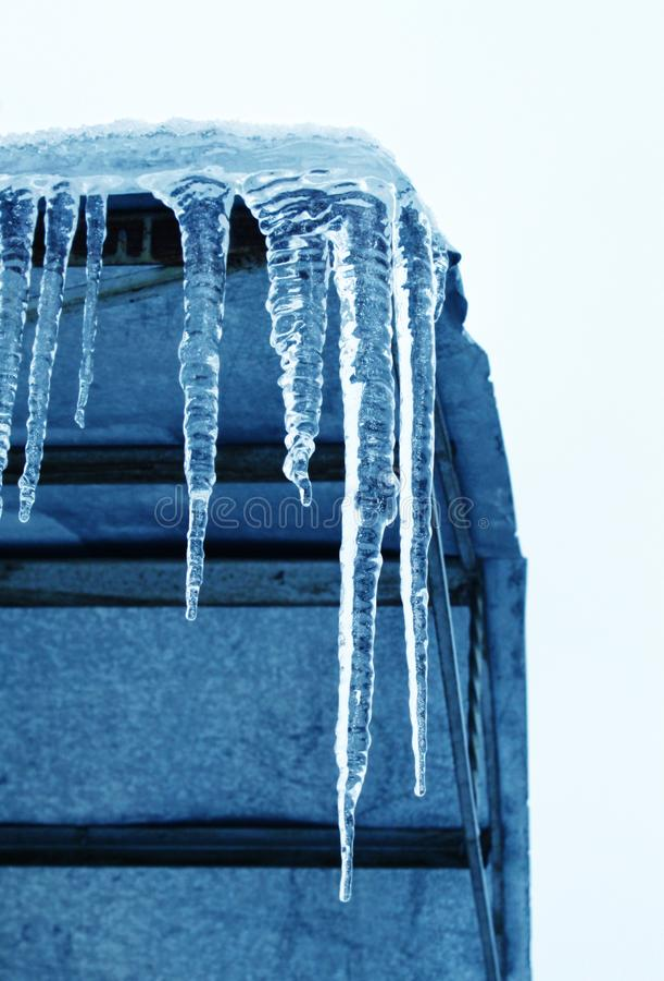 Grandi ghiaccioli che pendono dal tetto all'angolo della costruzione fotografia stock libera da diritti