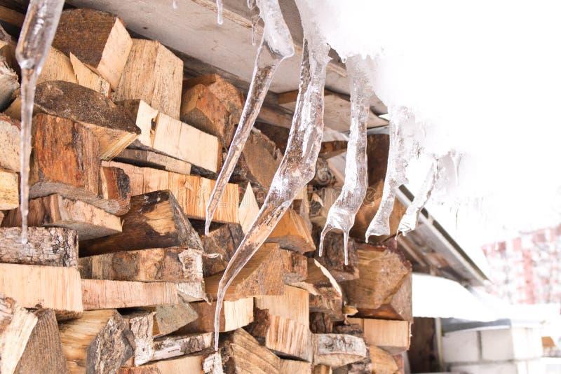 Grandi ghiaccioli divertenti che pendono dal tetto Fine in su immagine stock