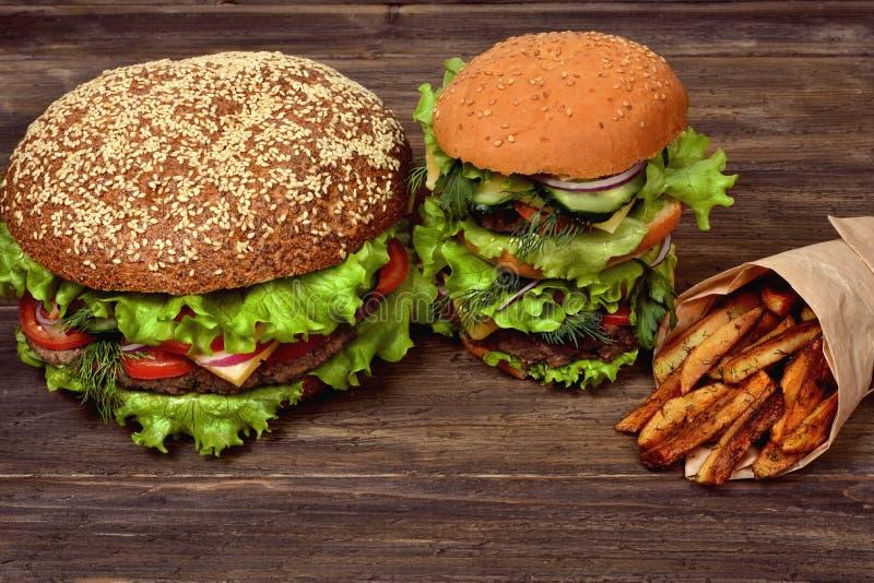 Grandi hamburger con le patate fritte per uno spuntino rapido immagine stock