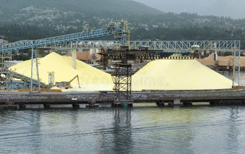 Grandi mucchi dello zolfo a porto industriale a Vancouver immagini stock