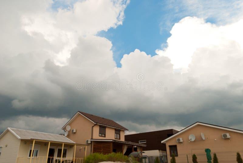 Grandi nuvole bianche contro il cielo blu blu al fondo della casa con bello giorno di estate del paesaggio dei differenti tetti p fotografia stock libera da diritti