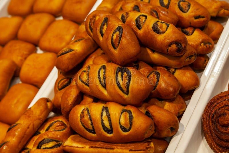 Grandi panini dorati appetitosi con i papaveri sotto forma di rotoli, co fotografia stock libera da diritti