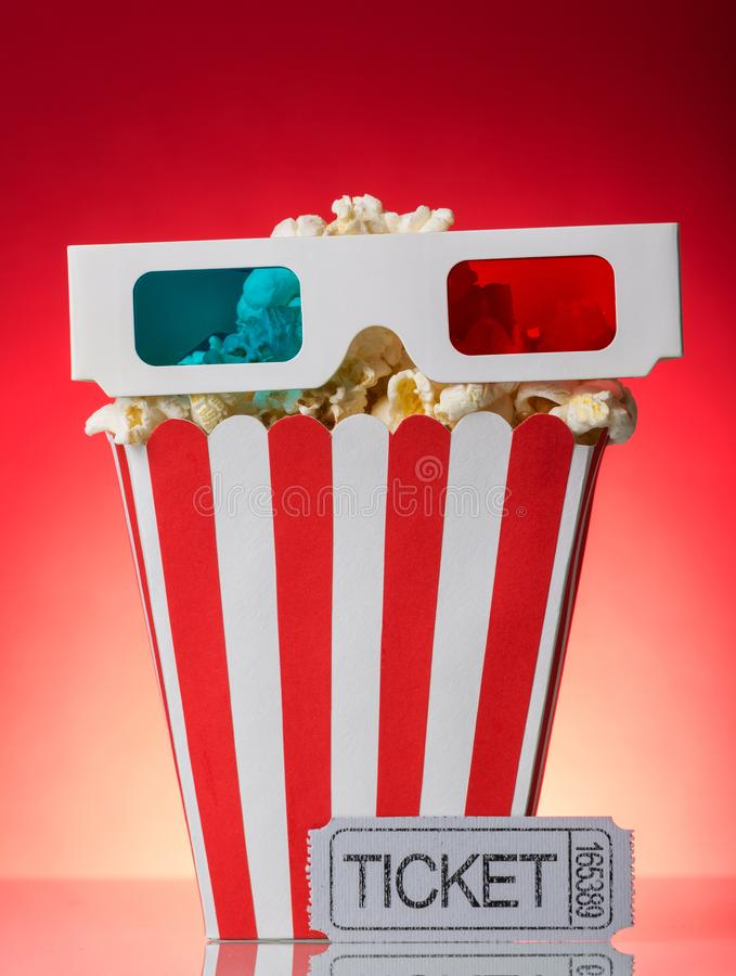 Grandi popcorn della scatola quadrata, vetri 3D e biglietto di film su luminoso fotografie stock libere da diritti