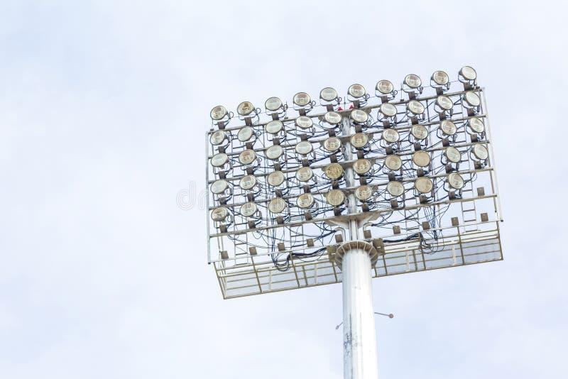 Grandi riflettori allo stadio all'aperto sotto il cielo blu immagine stock libera da diritti