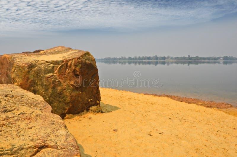 Grandi rocce sulla spiaggia di sabbia accanto al chiaro lago blu fotografie stock libere da diritti