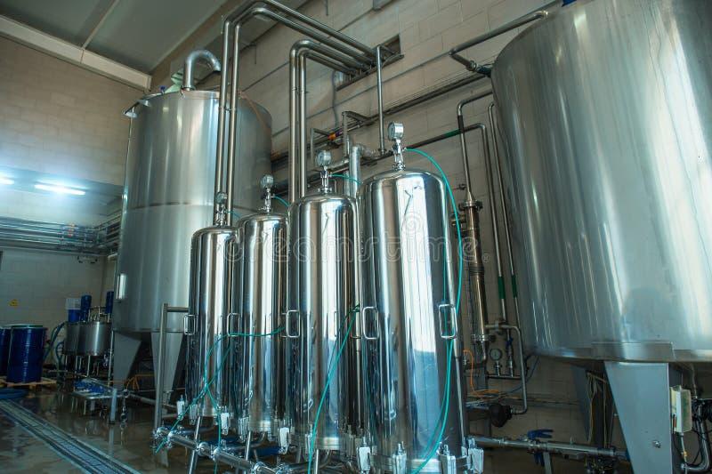 Grandi serbatoi o tini di acciaio dentro l'interno dell'impianto di produzione dell'acqua e del succo immagine stock libera da diritti