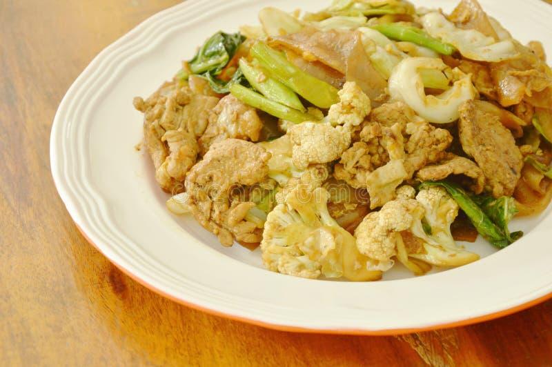 Grandi tagliatelle di riso fritte con carne di maiale e la verdura in salsa di soia nera sul piatto fotografia stock libera da diritti